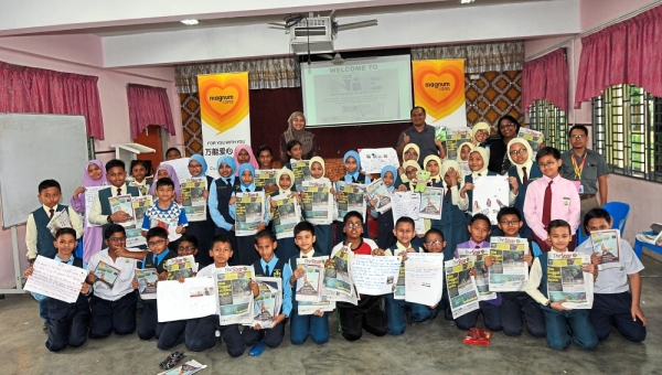 """Group photo of the pupils and teachers during the Star-NiE English workshop at SK Taman Impian Emas in Johor Baru. (Right) Pupils in action during the 'cut and paste' activities using newspaper clippings. """""""" Photos: ABDUL RAHMAN EMBONG/The Star"""