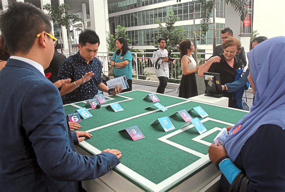 Two guests trying to beat each other in a game of football cards.