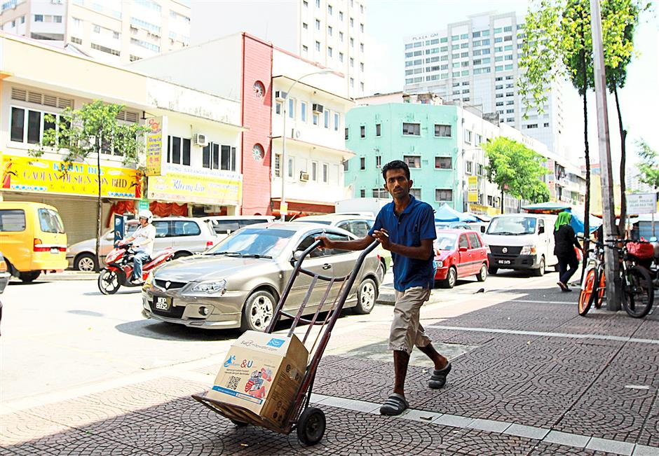 Busy work place: Workers transporting goods here and there is a common sight in Lorong Haji Taib during the day, before the sex workers come out for business when night falls.