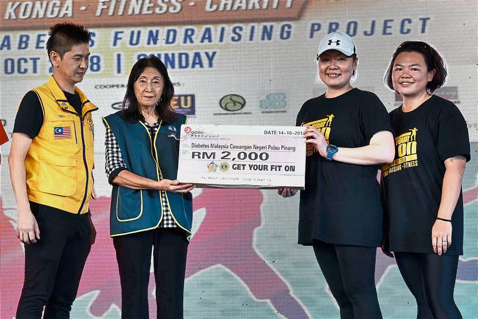Event organising chairperson Young Ming Hoe (left), Lions Club of Tanjung Putri president Sylvia Ang (second right) and Chan (right) presenting the RM2,000 mock cheque to Soon during the 'Get Your Fit On' event.