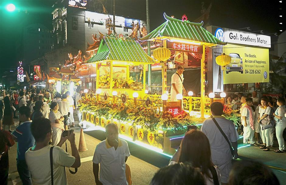 (Above) A brightly lit float among the highlights of the procession outside the Kuan Im See Temple in Burmah Road, George Town.
