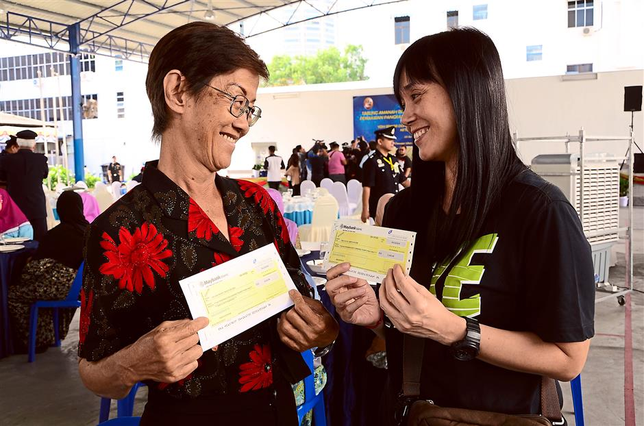 Every bit helps: (From left) Ng and another recipient Tong Fui Fui showing the cheques they received from the Warrior and National Defence Trust Fund.