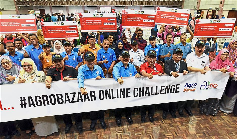 Ishak (front row fifth left) flanked by Ahmad (on his right), Politeknik Seberang Perai director Mohd Fisal Haroon, with officials and grant recipients after launching the Agrobazaar Online Challenge 2019 programme at Politeknik Seberang Perai in Bukit Mertajam. — MUSTAFA AHMAD/The Star