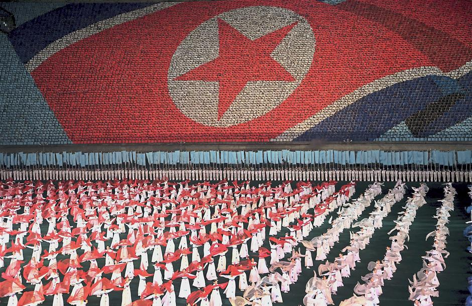Full of grace: North Korean women dancing in front of a display of their countryu2019s national flag in Pyongyang. u2014 AP