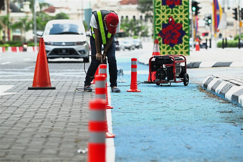 DBKL worker installing orange flexi-poles to demarcate the bicycle lane. This will not only improve safety for cyclists but also prevent motor vehicles from parking on the blue lane.