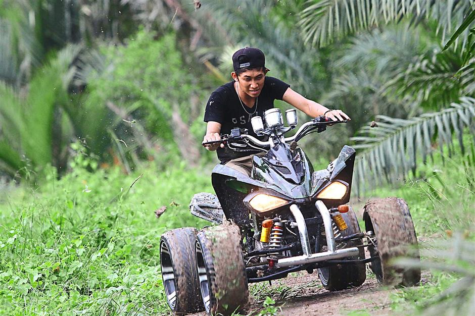 An ATV enthusiasts going on the mud with greenery in the background along the track in Pasir Penambang, Kuala Selangor