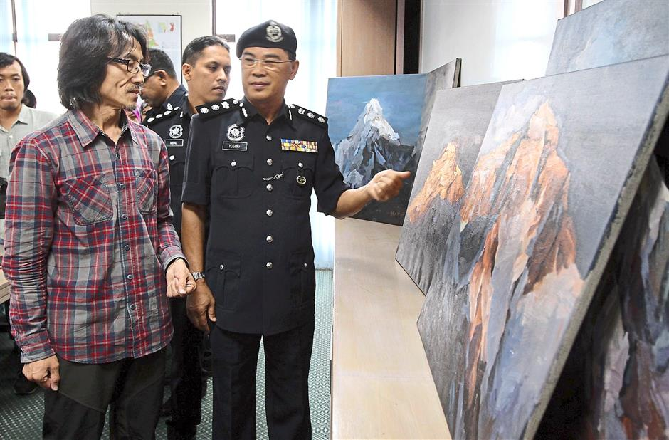Grateful: Chen (left), who holds the record for being the first person to paint from a height of 2,133m above sea level, and ACP Mohd Yusoff looking at the recovered artworks.