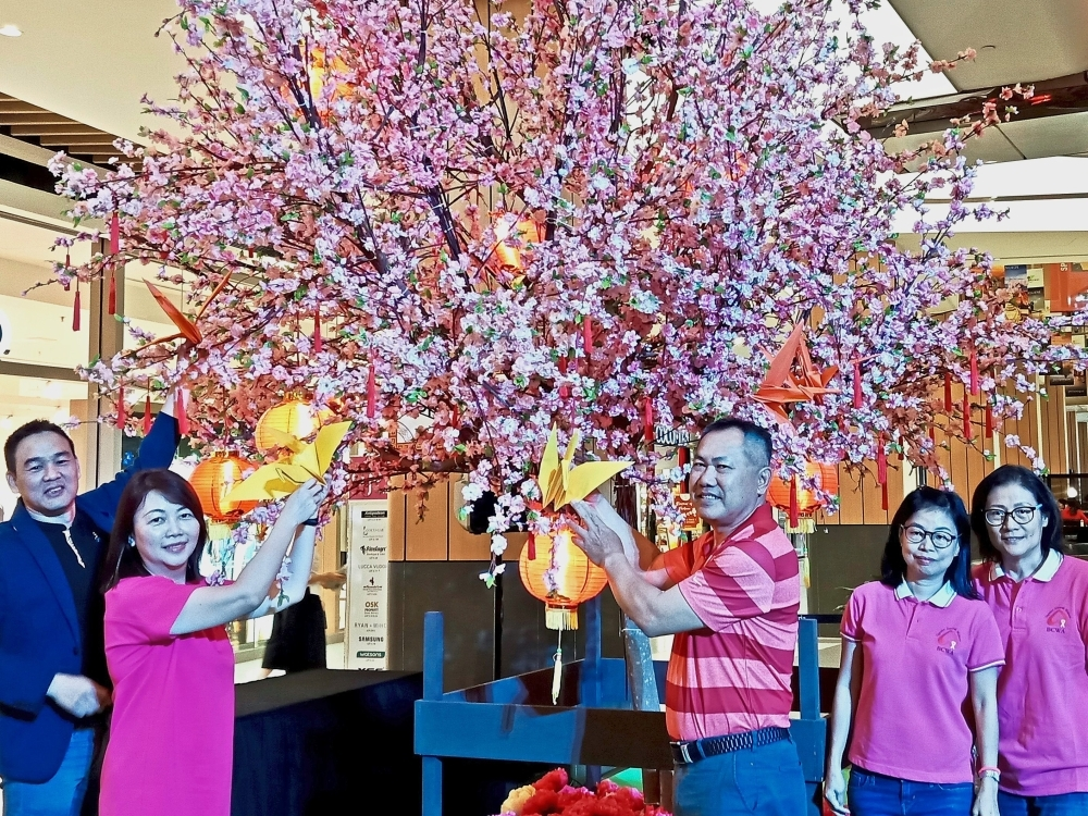Placing origami cranes on the cherry blossom tree to launch the 'Cut for Cancer' carnival at Atria Shopping Gallery are (from left) Lee, Caroline, Billy, Siew and BCWA Malaysia member Chan Yim Mei.