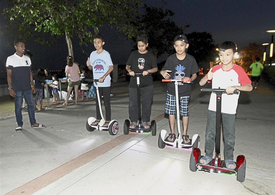 Mohd Andy Hakimi Abdullah (second from right), 10, and his friends enjoying their rides on Ninebot scooters.