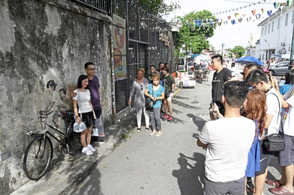 Tourists queuing to take photos with the Children on a Bicycle mural beside the cafe. (Right) Tourists still queuing up for photos with the mural after the illegal cafe extension has been demolished.