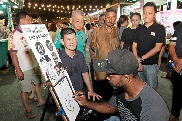 Cartoonist Mohd Azmi drawing a caricature of Ong during the food truck carnival at the car park of the Batu Lanchang Market in Penang. (Left) Customers waiting and taking their meals at the tables set up at the carnival.