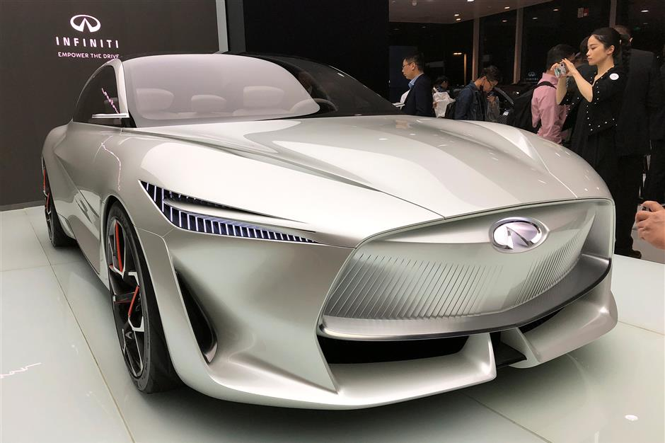 A woman takes picture of Infiniti\'s Q Inspiration concept car at an event in Beijing, China April 23, 2018.   REUTERS/Joe White