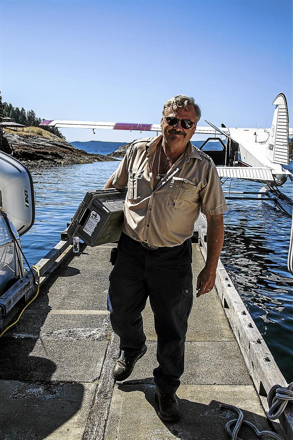 Pilot Mike Farrell lugging a box of mail at Refuge Cover, W. Redonda Isle. - Photo by Steve Haggerty/ColorWorld/MCT