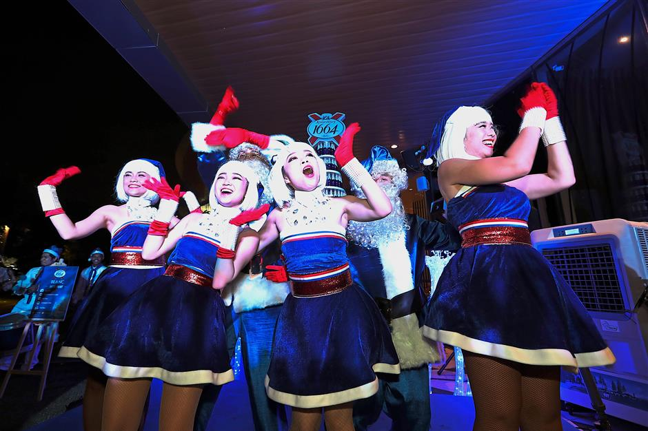 (Above) Blue Santarinas break into a dance to celebrate the lighting up of the Kronenbourg 1664 Blanc blue Christmas tree. (Left) Guests in the giant roving snow globe with a blue Santa during event.