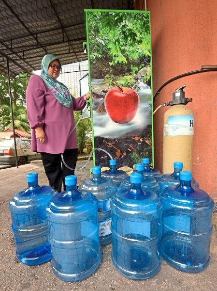 Azlin Yahya, 48, buying drinking water at a dispenser near her home in Bangsar Utama, Kuala Lumpur, in preparation for the scheduled cut. — Photos: AZHAR MAHFOF, RAJA FAISAL HISHAN, AZMAN GHANI and FAIHAN GHANI/The Star