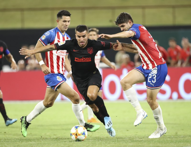 Jul 23, 2019;  Arlington, TX, USA; Atletico Madrid forward Angel Correa (10) fights his way past Guadalajara midfielder Carlos Villanueva (23) during the second half in the International Champions Cup soccer series at Globe Life Park. Credit: Kevin Jairaj-USA TODAY Sports