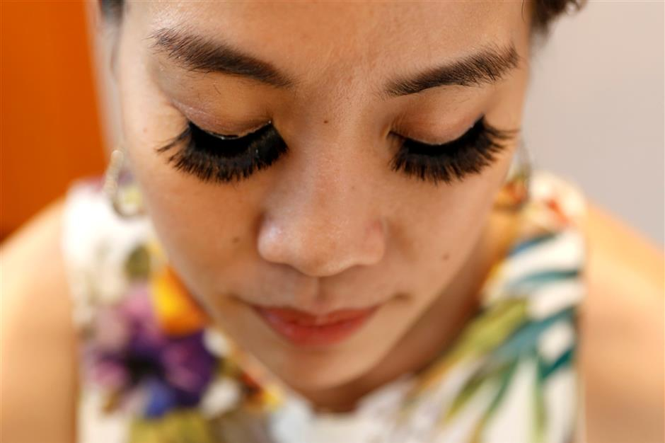 A woman wears fake eyelashes by e-commerce brand Bohktoh in Bangkok, Thailand June 12, 2019. Picture taken June 12, 2019. REUTERS/Jiraporn Kuhakan NO RESALES. NO ARCHIVES.