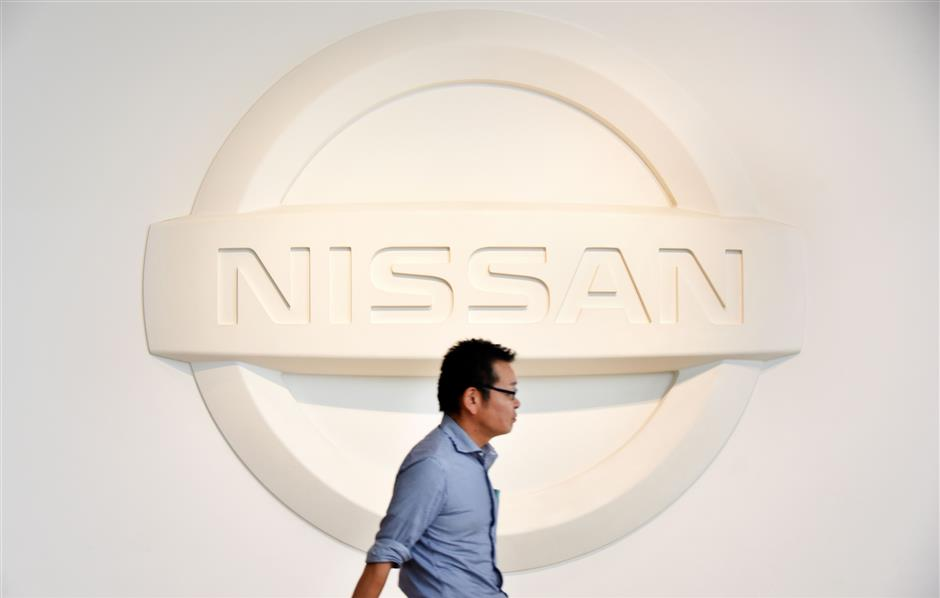 (FILES) This file photo taken on July 27, 2017 shows a man walking past a logo of Japan\'s automaker Nissan Motor at a showroom in Yokohama. Scandal-hit Nissan said on November 8, 2017 it had downgraded its forecast for annual operating profit, after an inspection scandal in its home market Japan. / AFP PHOTO / Toru YAMANAKA