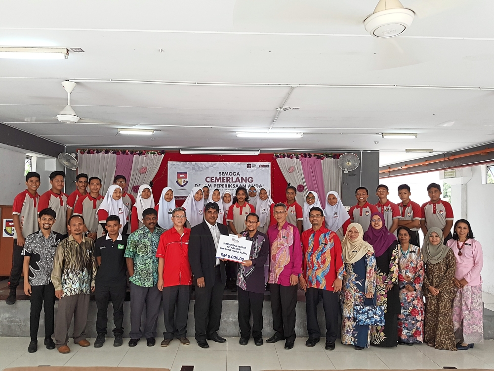 Mohandass (sixth from left) presenting the cheque to Sabri. With them are Farouk (left), Ikhmal (third from left), Sri Muhunan (fourth from left), SMK Bukit Tinggi Parent-Teacher Association president Leong Yeon Thoon (fifth from left), Nadiathul (second from right) as well as school supervisors, teachers and some of the cricket players.