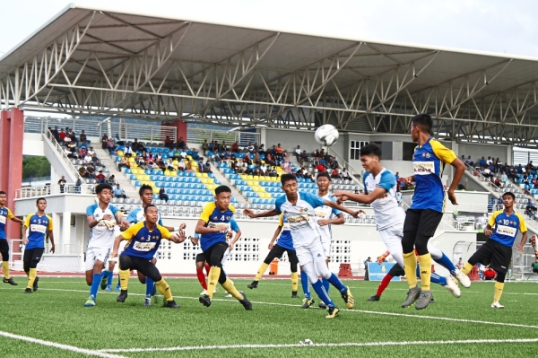SMK Tinggi Kajang players (in white and blue jersey) attacking SMK Datou2019 Harunu2019s goalmouth during the match.