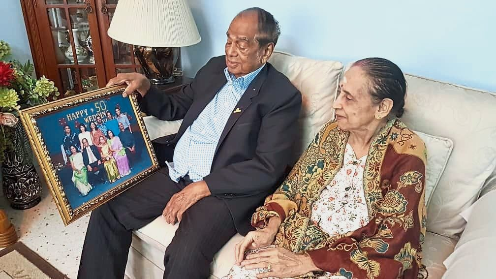 Subramaniam and Perumaiyee sharing a happy moment as they look at their 50th wedding anniversary celebration photo.
