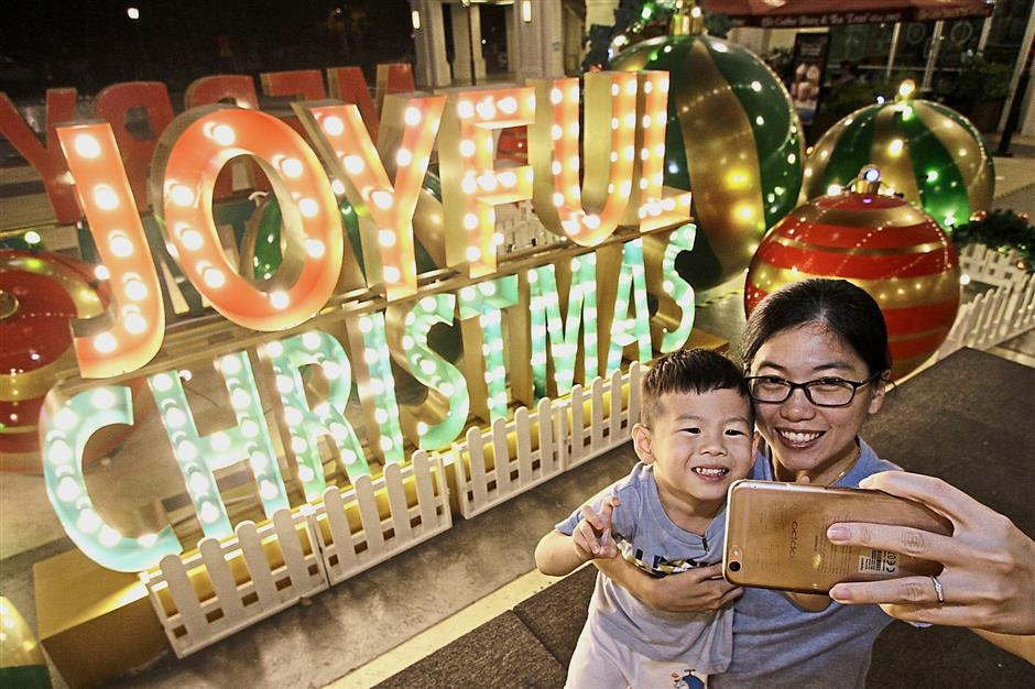 Fione Ooi, 36, taking a selfie with her three-year-old son Zhe against the Christmas sign with giant ornaments at Straits Quay Retail Marina.