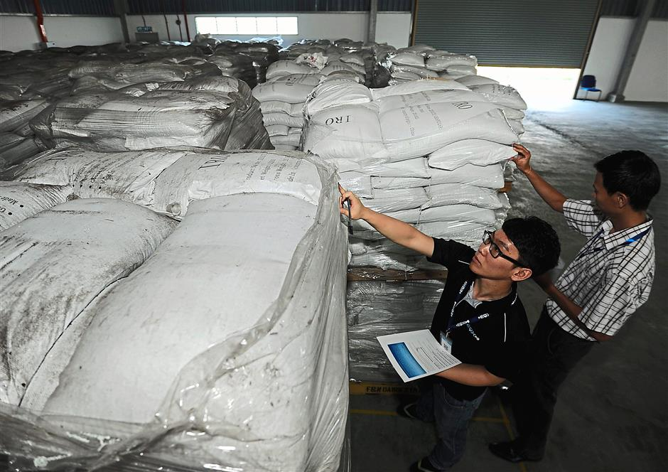 Tedious task: Workers checking industrial chemical stock at the factory.