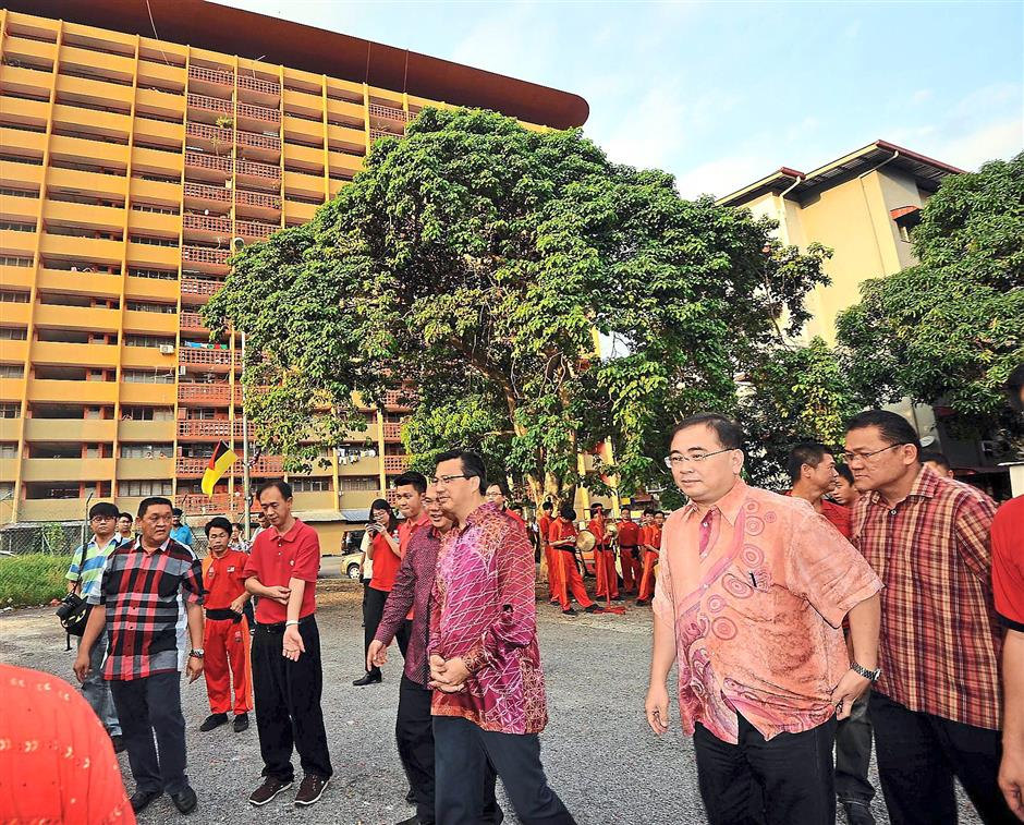 Walkabout: Liow (third from right) and Dr Wee (second from right) being taken on a tour of Templer Flats.