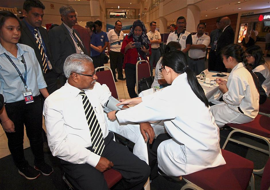 Perak exco A. Sivanesan having his blood pressure checked during the launching ceremony of Quest International University Public Health Awareness Campaign 2018 in Ipoh