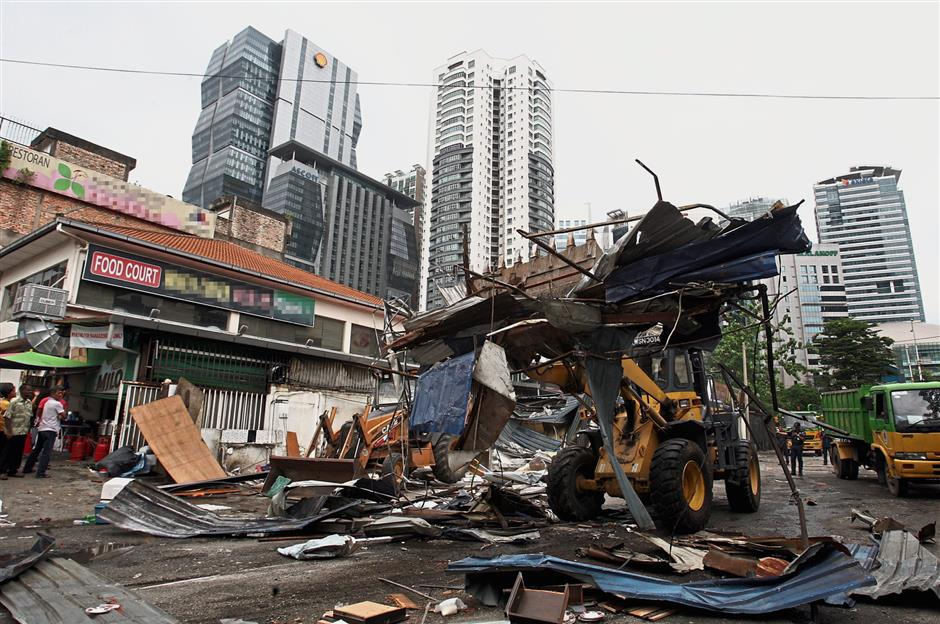 A backhoe tractor from DBKL tearing down a row of seven stalls operating illegally in a private open-air parking lot along Jalan Tun Sambanthan in Brickfields.