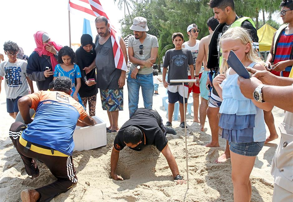 First time in 20 years: Members of the fisheries team carefully locating the turtle eggs and transferring them into a polystyrene box (inset) as tourists look on at Batu Ferringhi in Penang. — GOH GAIK LEE/ The Star