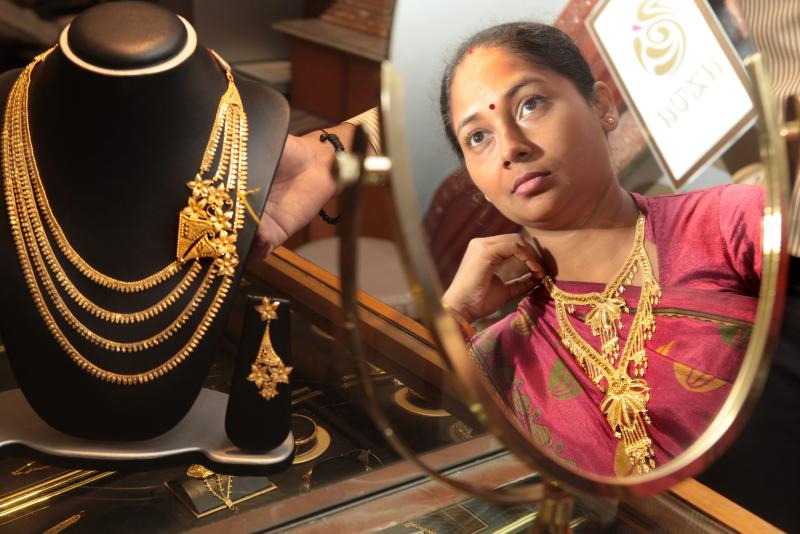 A woman eyes gold jewellery at Senco gold jewellery shop in Calcutta, eastern India, Aug 30, 2013. Battling a huge trade deficit and a weak currency, the government has taken various steps this year to make it harder and more expensive for Indians to get hold of gold - EPA Photo.