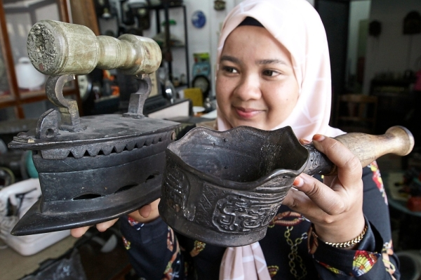 Nur Ain showing the different types of antique iron in her collection.