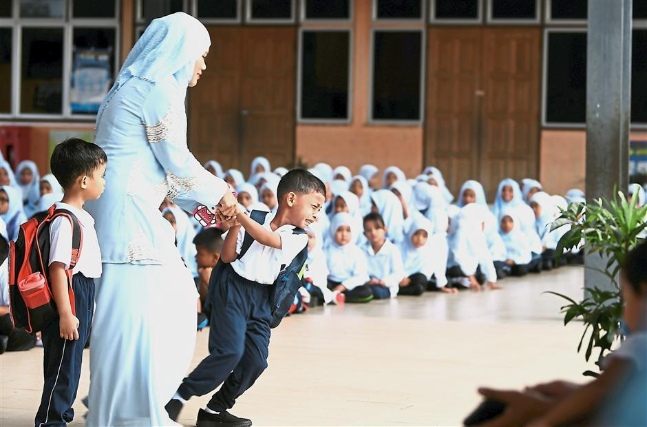 It's alright: Noraini, a teacher at SK Sungai Serai in Kuala Lumpur, trying to calm Year One pupil Mohd Firdaus Yahya who refused to join the school assembly. — Bernama