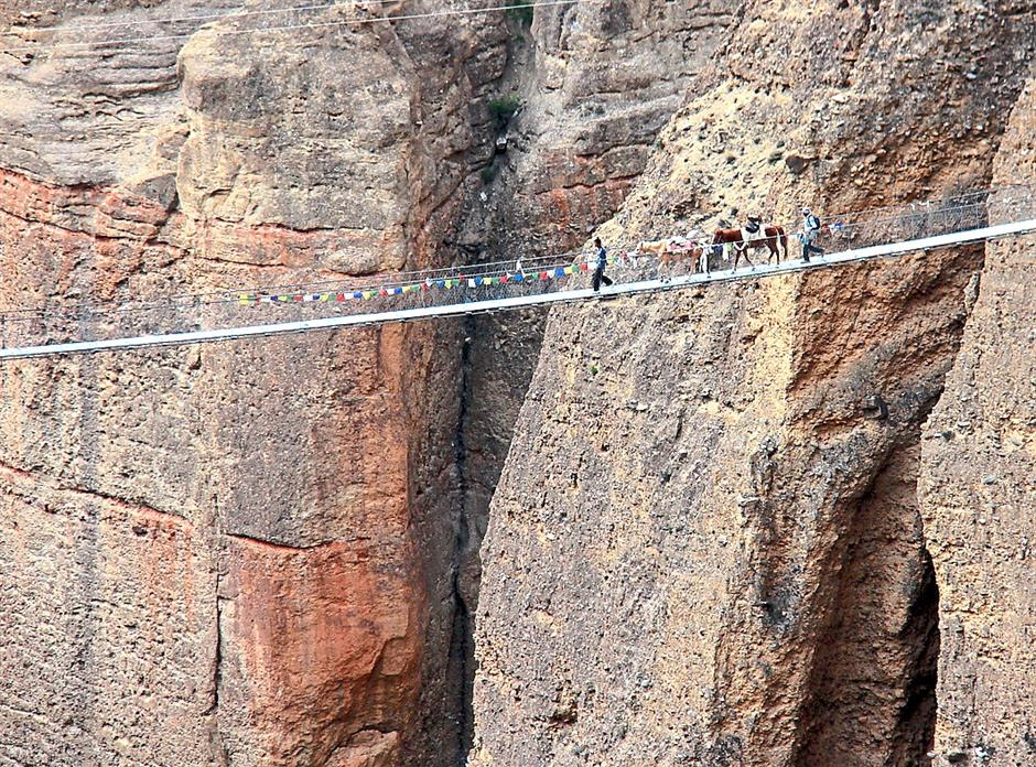 Horses crossing a suspension bridge.