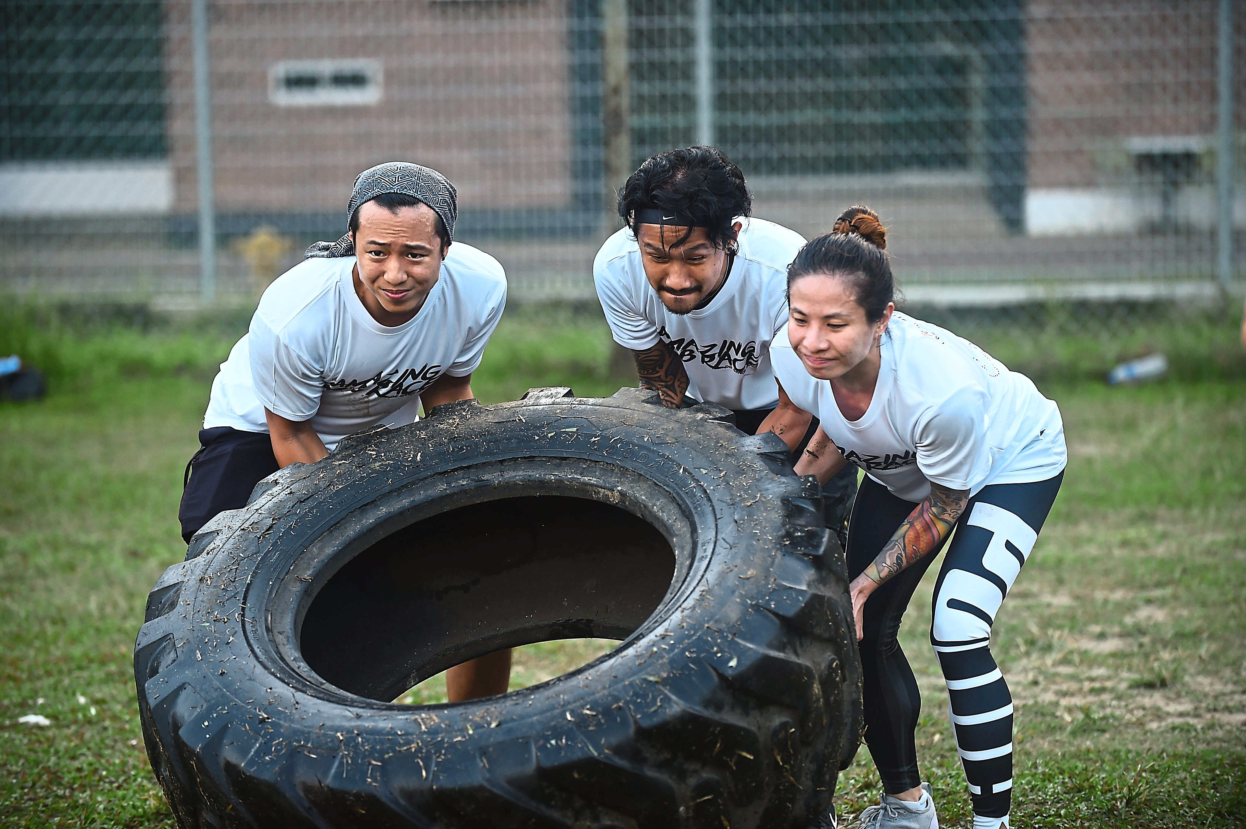 A team working together to flip a tyre across the field in once of the challenges.