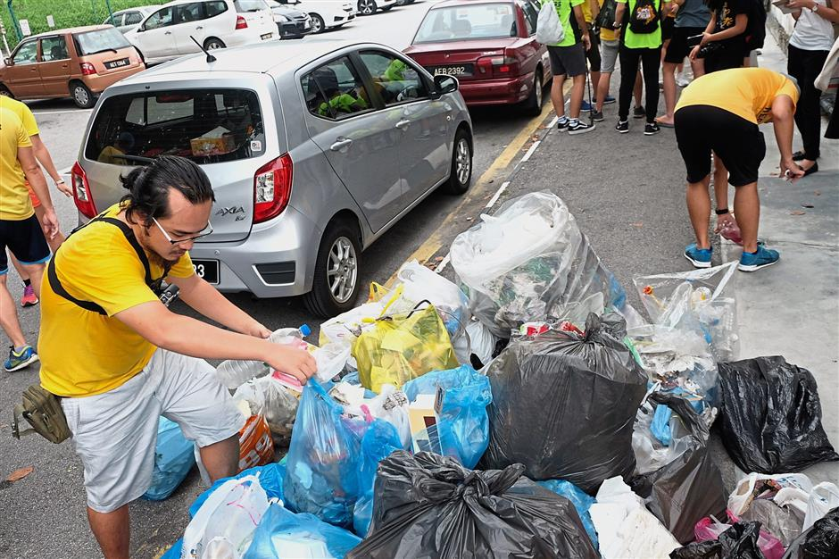 Foo (left) securing bags of rubbish picked up throughout the JOGJap Bersihkan Ipoh event.