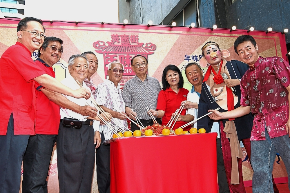Fong (sixth from left) and Ng (fourth from right) with other organisers of the event tossing yee sang.