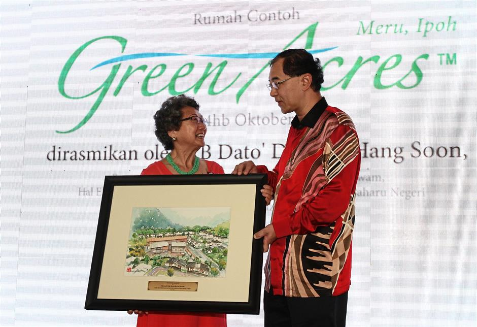 ipagreen241015 6... State executive councillar Datuk Dr Mah Hang Soon (right) receiving a souvenir from Total Investment Sdn Bhd co-founder Siew Yin Leng during the launching of show units of GreenAcres Retirement Village at Bandar Meru Raya, Ipoh on Oct 24.
