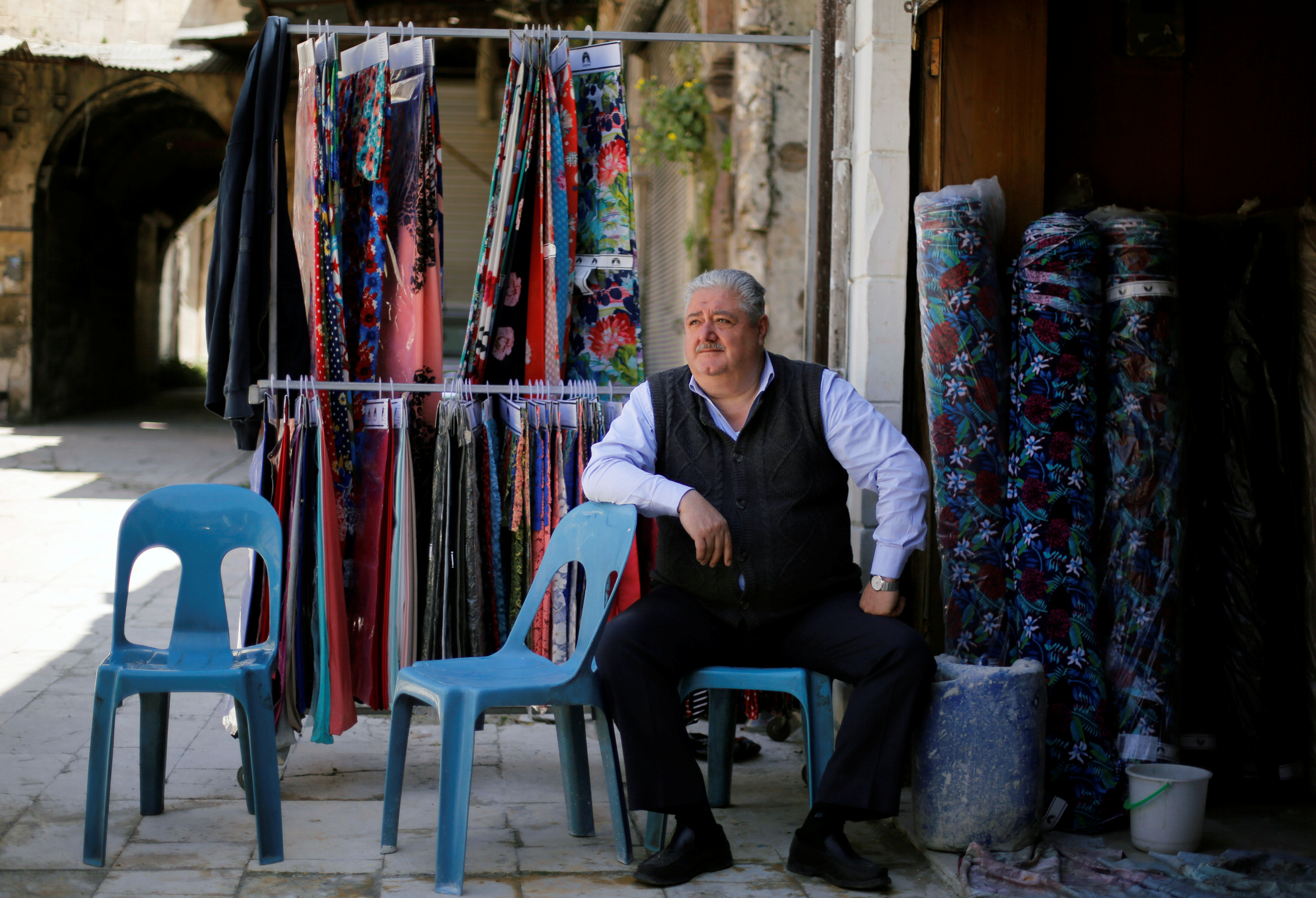 FILE PHOTO: A Syrian merchant sits at Mohammed Abu Zeid's shop in Khan Khair Bek at the old city of Aleppo, Syria April 13, 2019. REUTERS/Omar Sanadiki