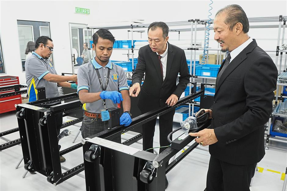 (From right) Ng and Lau inspecting one of their production lines at the new UWC plant located in Batu Kawan, Penang.