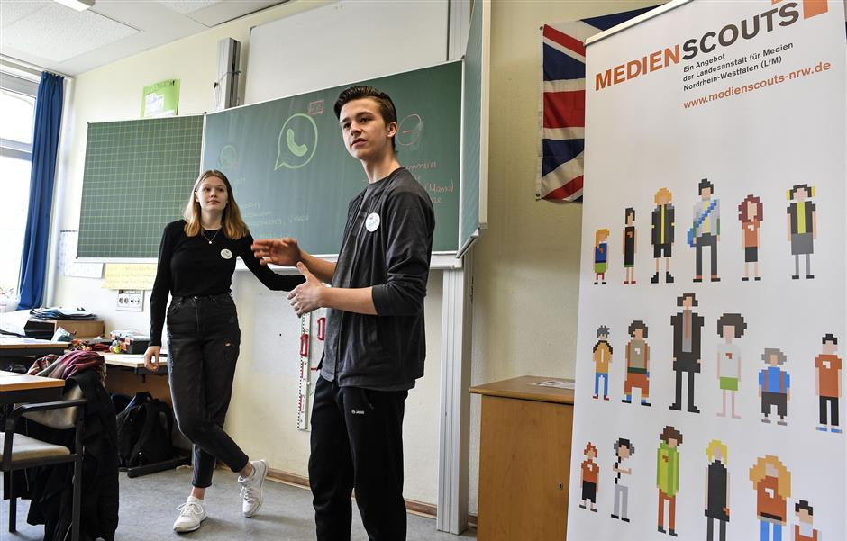 Senior students and media scouts Leon Zielinski, right, and Chantal Hueben teach young pupils during a lesson in social media and internet at a comprehensive school in Essen, Germany, Monday, March 18, 2019. According to experts and teachers the peer projects in which teenagers teach their younger schoolmates how to stay safe and sane online have proven to be especially successful.  (AP Photo/Martin Meissner)