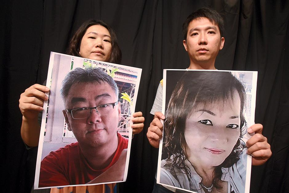 Help them: Chan showing a photo of her husband Then and Chung holding a picture of his mother Thien. Both are still being held hostage in the Philippines.