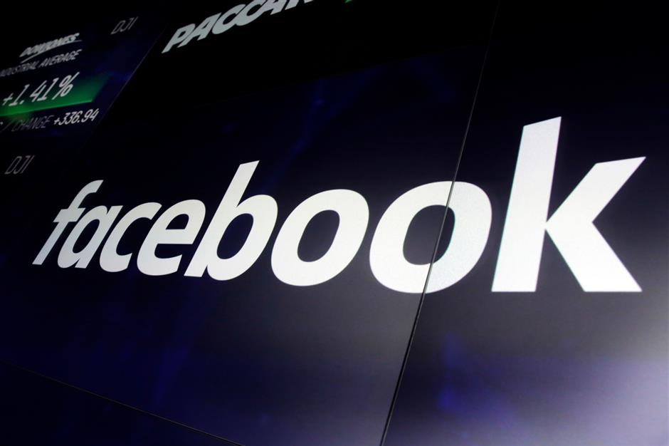 FILE - In this Thursday, March 29, 2018, file photo, the logo for Facebook appears on screens at the Nasdaq MarketSite, in New York's Times Square. The question comes up over and over, with extremist material, hate speech, elections meddling, privacy invasions, housing discrimination. Why canu2019t Facebook just fix it? (AP Photo/Richard Drew, File)