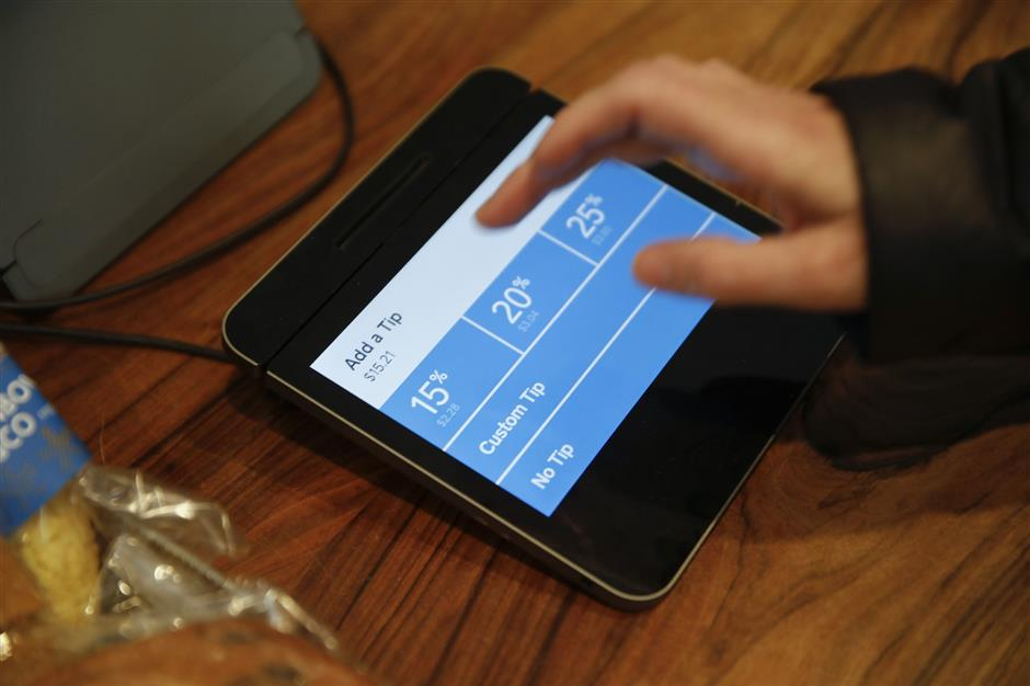 Christine Wickes, of Chicago, uses the technology to check out and then adds a tip at a Dollop coffee shop in the Streeterville neighborhood in Chicago (860 N. Dewitt Place) on Thursday, Nov. 29, 2018. The story is about how technology is transforming tipping, perhaps most evident when people swipe their credit cards at coffee shops and are confronted with a tip screen prompting them to add a tip for a service they may not have considered tipping for before.  (Jose M. Osorio/Chicago Tribune)