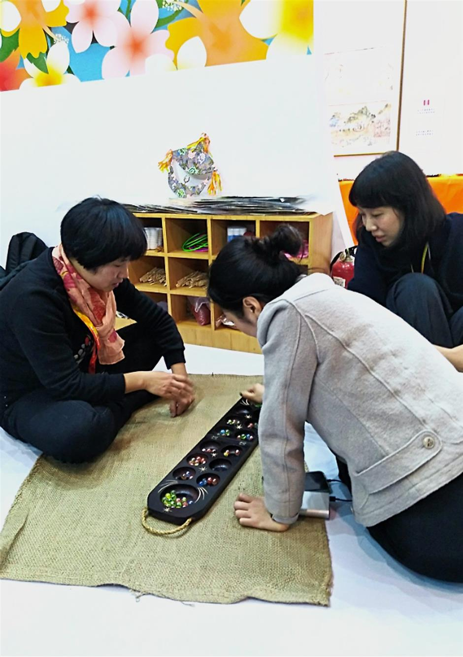 Traditional game: Visitors learning to play the congkak at the expo.
