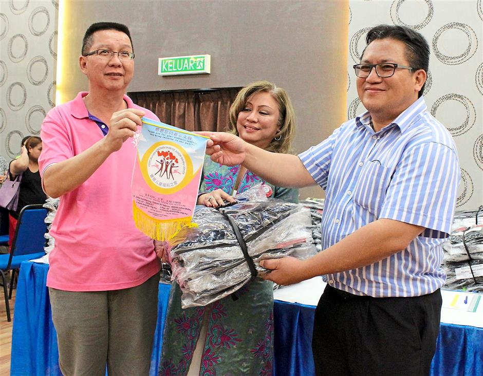 Nur Jazlan (right) and Goh (centre) handing over a bundle of school bags to a recipent's representative.