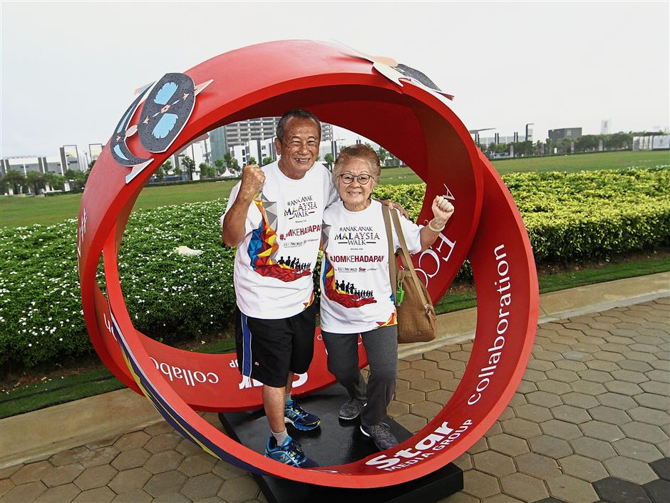 Agnes Teh, 73, and her husband Tan Ban King, 74, posing for a photo inside the giant red wristbands at Eco Horizon.