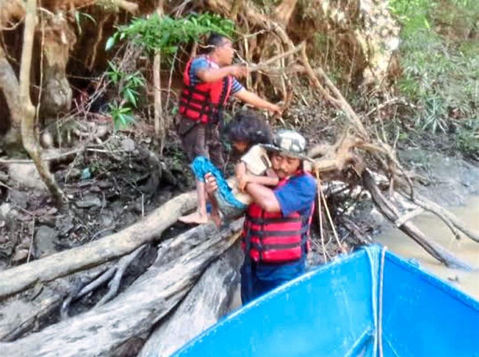 Miracle in the jungle: Rescuers  carrying Miksudiar onto a boat at Sungai Perias in Kampung Tohoi.