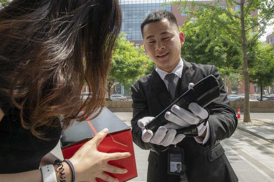 A driver for JD.com Inc.'s Luxury Express delivery service extends a handheld device for a customer to acknowledge receipt of her parcel in Beijing, China, on Thursday, May 16, 2019. Big names in luxury are teaming up with internet companies to offer sales and services like JD's white-gloved butler-style delivery that are rare in the U.S. Photographer: Gilles Sabrie/Bloomberg
